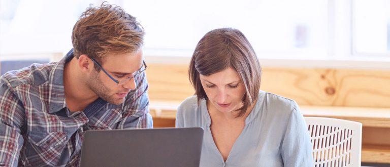 Kolleger som samarbeider foran laptop