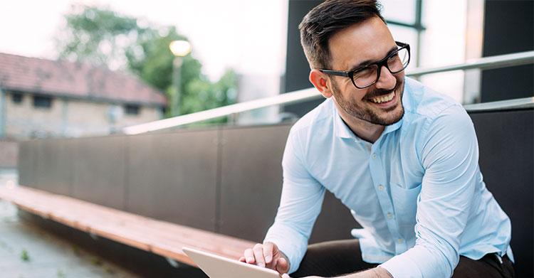 Mann som smiler med nettbrett