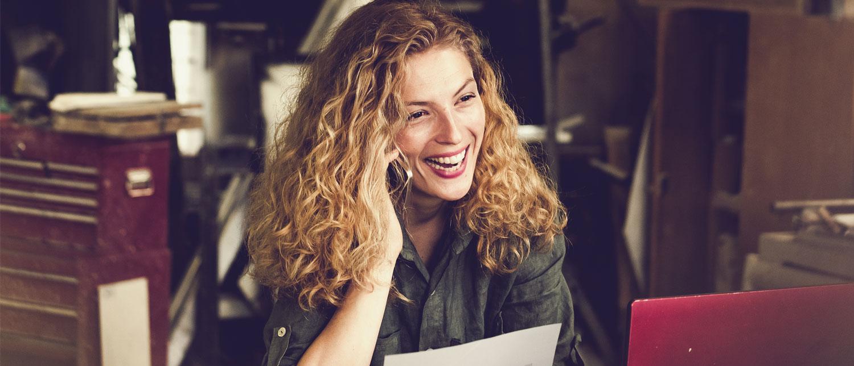 Smilende kvinne med en laptop som snakker i telefonen