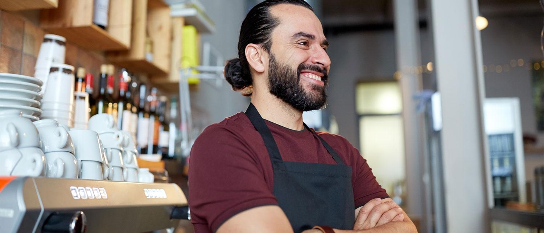 En smilende mann som jobber på kafé