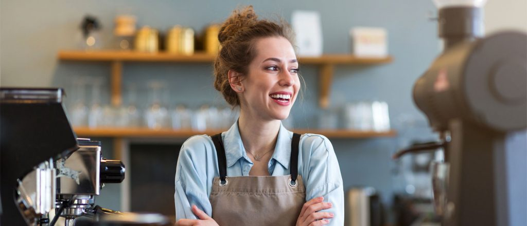 Smilende kvinne som arbeider i en kafé